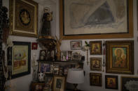 Religious elements decorate a bedroom at Joan Olmedillo's home in Barcelona, Spain, April 2, 2020. Olmedillo received a house call from visiting nurse Laura Valdes during the coronavirus pandemic. (AP Photo/Emilio Morenatti)