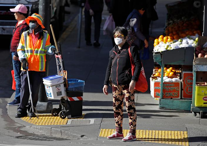 A masked worker and shopper wait for a street signal on Jan. 31, 2020, in the Chinatown district of San Francisco.