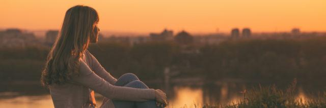 a woman is sitting watching the sunset