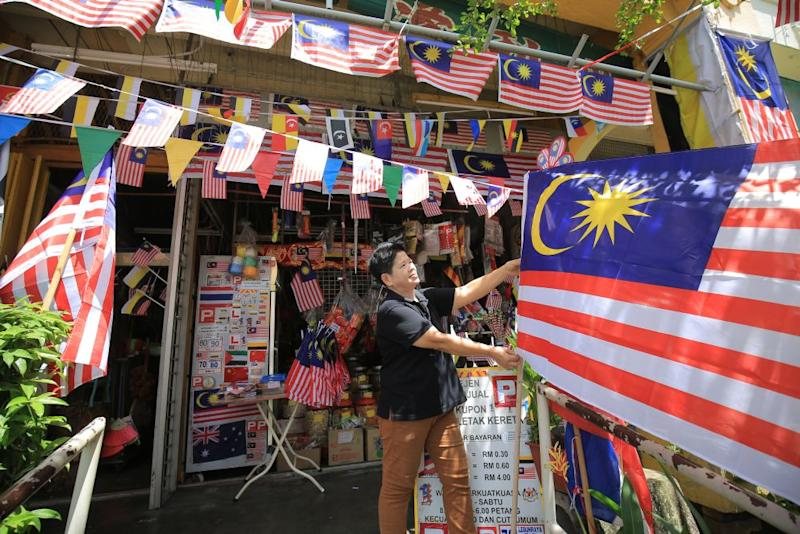 Fong Lee Seng Hup Kee store owner Lau Siew Ngor adjusts a Jalur Gemilang in front of her shop in Ipoh August 24, 2018. ― Pictures by Marcus Pheong