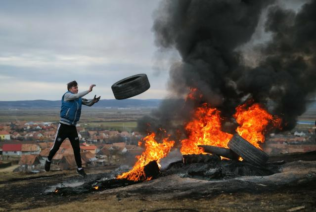 In this photo taken on Sunday, March 10, 2019, a young man throws a tire during a ritual marking the upcoming Clean Monday, the beginning of the Great Lent, 40 days ahead of Orthodox Easter, on the hills surrounding the village of Poplaca, in central Romania's Transylvania region. Romanian villagers burn piles of used tires then spin them in the Transylvanian hills in a ritual they believe will ward off evil spirits as they begin a period of 40 days of abstention, when Orthodox Christians cut out meat, fish, eggs, and dairy. (AP Photo/Vadim Ghirda)
