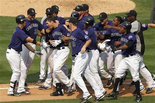 Colorado Rockies' Tyler Colvin, third from left, is surrounded by teammates after hitting a game-winning double against the Milwaukee Brewers in the bottom of the ninth inning of a baseball game, Wednesday, Aug. 15, 2012, in Denver. The Rockies won 7-6. (AP Photo/Barry Gutierrez)