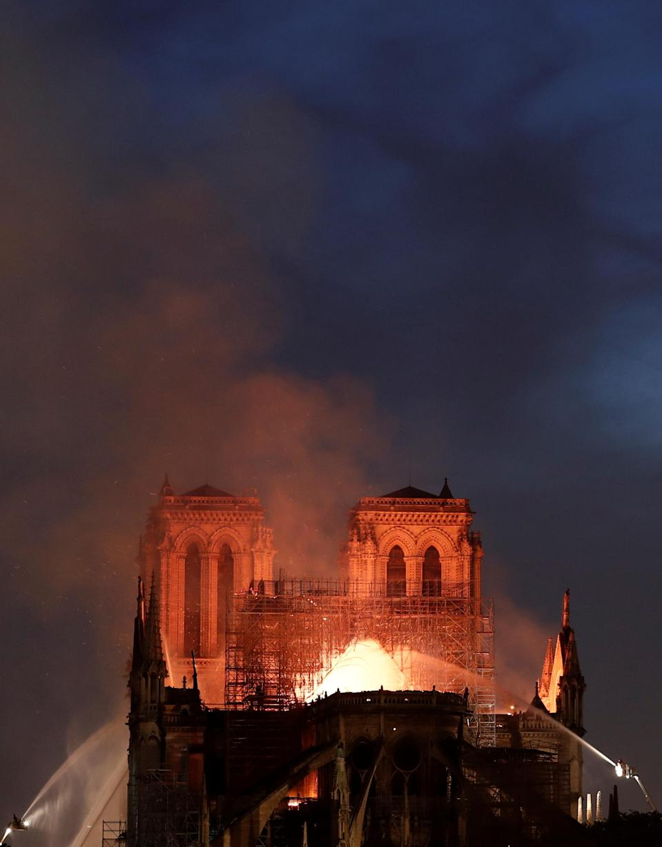 Firefighters douse flames from the burning Notre Dame Cathedral in Paris. Source: Reuters