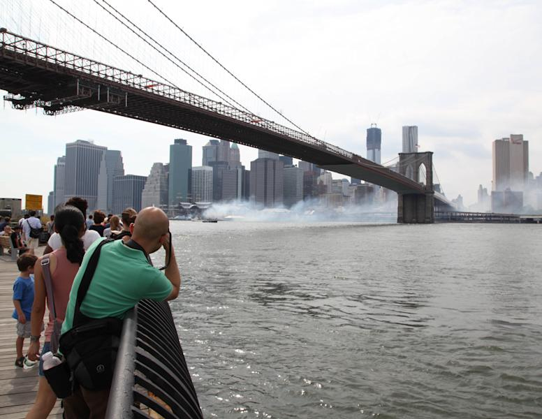 Smoke rises off Pier 17 and floats along the East River toward the Brooklyn Bridge as firefighters fight a three alarm fire at the South Street Seaport, Saturday, July 14, 2012 in New York. About 140 firefighters and the U.S. Coast Guard responded to the blaze that broke out about 4 p.m. Saturday. There were no injuries. (AP Photo/Lisa Tolin)