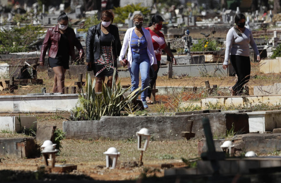 People arrive for the burial of Jose Mario de Souza Veiga, 83, whose family members said died of COVID-19, at the Campo da Esperanca cemetery on the border of the neighborhoods of Taguatinga and Ceilandia, in Brasilia, Brazil, Tuesday, July 21, 2020. (AP Photo/Eraldo Peres)