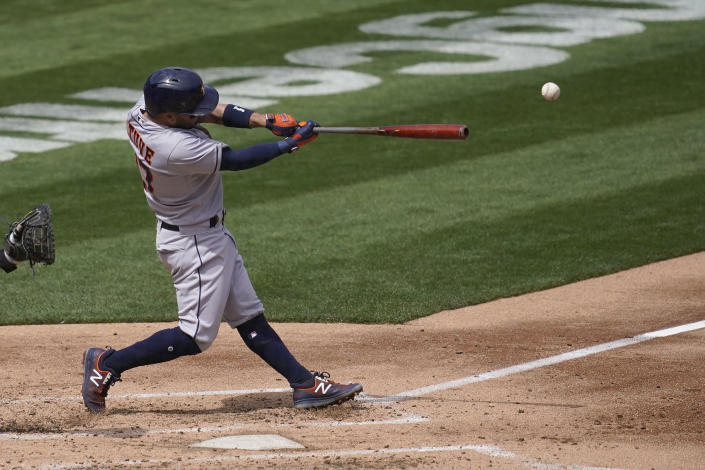 Houston Astros' Jose Altuve hits an RBI-single against the Oakland Athletics during the second inning of a baseball game in Oakland, Calif., Saturday, April 3, 2021. (AP Photo/Jeff Chiu)