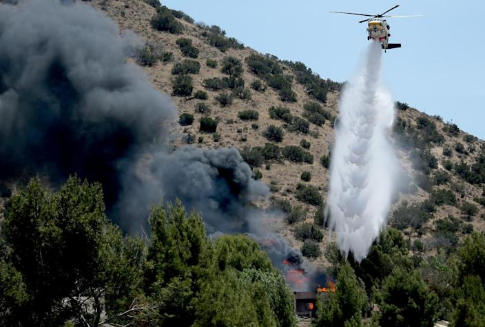 Above a scrub-covered hillside a helicopter hovers and releases a white plume on a burning structure.