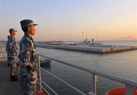 Chinese naval soldiers stand guard on China's first aircraft carrier Liaoning, as it travels towards a military base in Sanya