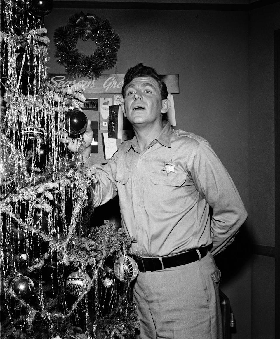 <p>Television legend Andy Griffith celebrated the season while on the set of <em>The Andy Griffith Show</em> in his sheriff uniform, of course. The actor decorated a Christmas tree with his costars for the episode.  </p>