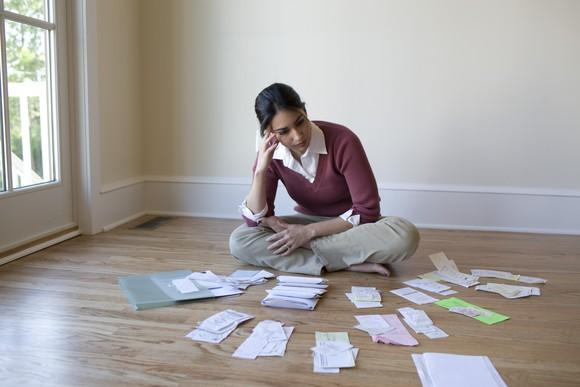 Woman with receipts and paperwork spread out on the floor