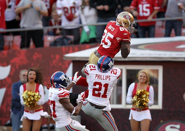 SAN FRANCISCO, CA - NOVEMBER 13: Vernon Davis #85 of the San Francisco 49ers jumps over Kenny Phillips #21 and Michael Coe #37 of the New York Giants for a touchdown at Candlestick Park on November 13, 2011 in San Francisco, California. (Photo by Ezra Shaw/Getty Images)