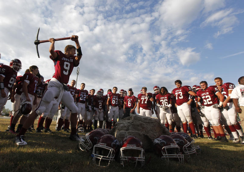 Joplin High School wide receiver Colton Simmons uses a pick to hit a rock before their home-opener in Joplin, Mo., Saturday, Sept. 10, 2011. The tornado that swept through in May of 2011 took homes and businesses, friends and families as it killed more than 150 people and left billions of dollars in damage. There's comfort in routine and the Joplin High football team will give thousands of them a chance for another step toward normalcy on Saturday night when the Eagles play a home opener like none other around here.   (AP Photo/Paul Sancya)