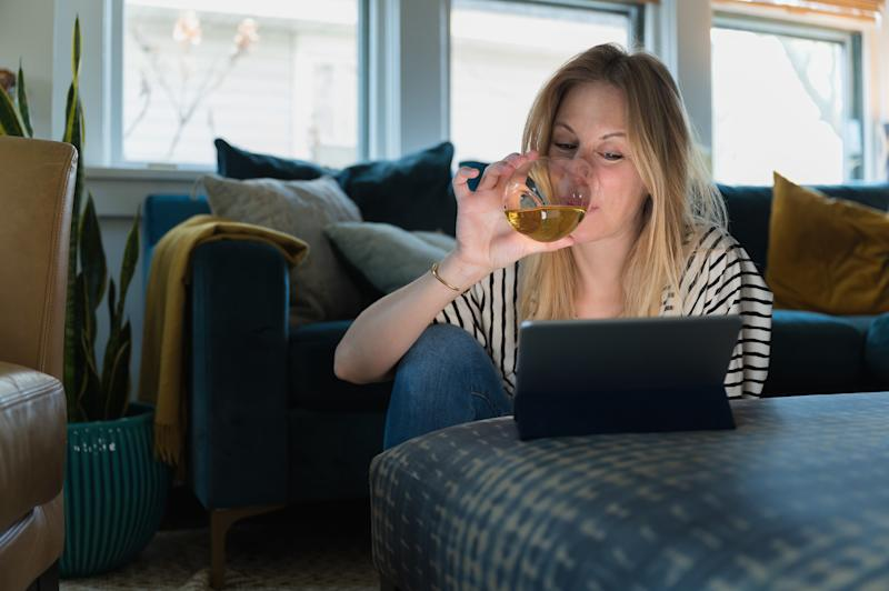 Woman drinking wine and looking at tablet at home