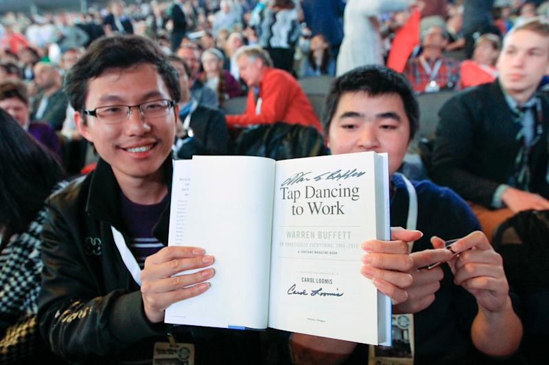 Wei Huang from Shenzhen, China, left, displays a book autographed by Warren Buffett as he waits with other shareholders for the Berkshire Hathaway shareholders meeting to begin, in Omaha, Neb., Saturday, May 4, 2013. Tens of thousands attend Berkshire Hathaway shareholder meeting to hear Warren Buffett and Charlie Munger answer questions for more than six hours. No other annual meeting can rival Berkshire's, which is known for its size, the straight talk Buffett and Munger offer and the sales records shareholders set while buying Berkshire products. (AP Photo/Nati Harnik)