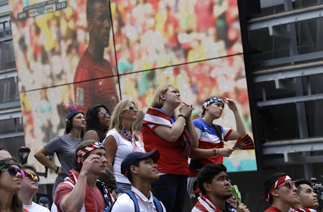 Soccer fans watch the World Cup Soccer match between the U.S. and Germany as a match between Portugal and Ghana plays in the background at Victory Plaza in downtown Dallas, Thursday, June 26, 2014. (AP Photo/LM Otero)