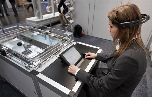 "A woman poses with a brain-computer interface (BCI), a solution for future human-machine cooperation, at the Festo stand during a guided press tour at the ""Hannover Messe"" industrial trade fair in Hanover April 22, 2012."