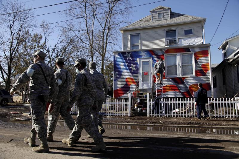 Members of the National Guard walk past a house damaged by Superstorm Sandy as it is painted with an American flag in the New Dorp section of Staten Island, New York, Tuesday, Nov. 6, 2012. Voting in the U.S. presidential election is the latest challenge for the hundreds of thousands of people in the New York-New Jersey area still affected by Superstorm Sandy. (AP Photo/Seth Wenig)