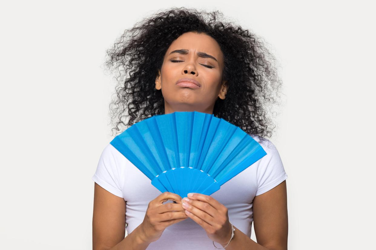 Overheated sweaty african woman holding blue handheld fan posing isolated on grey background. Female feels unwell cooling in summer weather, girl suffers from heat waving fan relief hot day concept