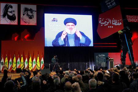 FILE PHOTO: Lebanon's Hezbollah leader Sayyed Hassan Nasrallah is seen on a video screen as he addresses his supporters in Beirut, Lebanon February 16, 2018. REUTERS/Aziz Taher/File Photo