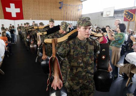 Recruits from the veterinary troops of the Swiss Army play traditional cow-bells during an official visiting day at a Swiss army base in Sand bei Schoehnbuehl, outside Bern September 7, 2013. REUTERS/Ruben Sprich
