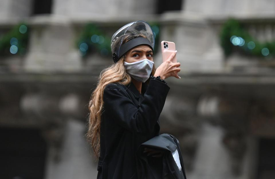 A woman wearing a face shield takes pictures with her mobile phone outside the New York Stock exchange (NYSE) at Wall Street on November 30, 2020 in New York City. - Credit ratings giant S&P Global reached an all-stock deal to buy IHS Markit for $44 billion, creating a massive enterprise to produce data and analytics used by Wall Street, the companies announced Monday. (Photo by Angela Weiss / AFP) (Photo by ANGELA WEISS/AFP via Getty Images)