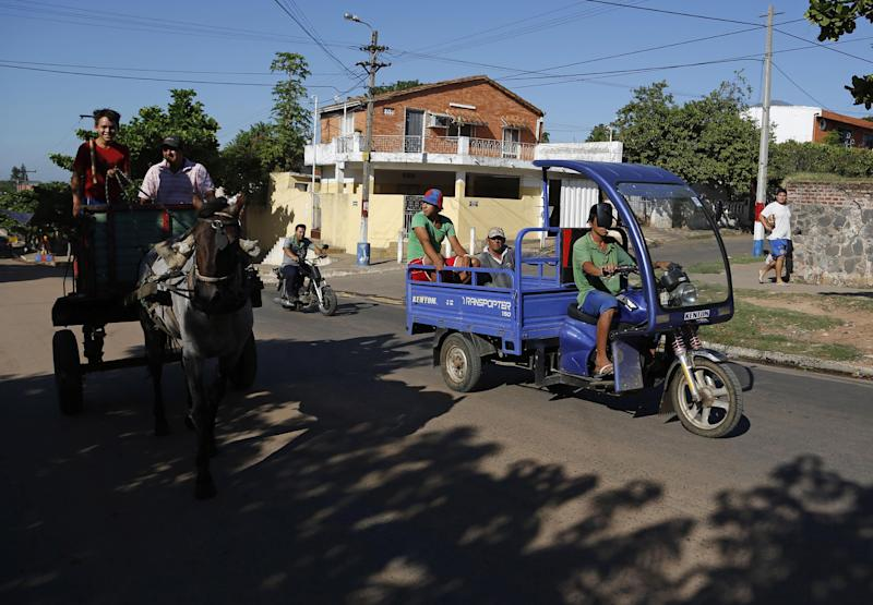 A motorcycle driver passes a horse-drawn cart in the Tacumbu neighborhood of Asuncion, Paraguay, Thursday, Jan. 30, 2014. The city is phasing out the horse-drawn carts used by people who collect recyclable material and is sending the horses to an equine sanctuary, replacing the horse-drawn carts with moto-carts. The Leopard company that makes many of the carts is offering credit to impoverished junk collectors with no collateral so they can slowly pay off the $4,000 price. (AP Photo/Jorge Saenz)
