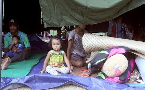 A family rest in a tent at an evacuee camp in Klungkung - Credit: AP Photo/Firdia Lisnawati
