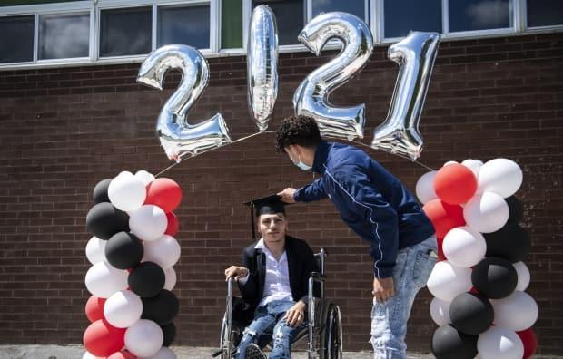 Mustafa Hassun, right, adjusts his brother Halid's mortarboard as he gets ready to have a photo taken under the balloon arch during graduation at Ottawa's Gloucester High School last week. (Justin Tang/The Canadian Press - image credit)