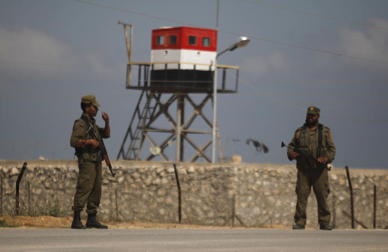 Palestinian Hamas security guards stand near an Egyptian watch tower on the border with Egypt in Rafah, southern Gaza Strip, Friday, July 5, 2013. Egyptian official said the country's border crossing with Gaza Strip in northern Sinai has been closed indefinitely, citing security concerns. The decision comes hours after suspected Islamic militants attacked four sites in northern Sinai, targeting two military checkpoints, a police station and el-Arish airport, where military aircraft are stationed. (AP Photo/Hatem Moussa)