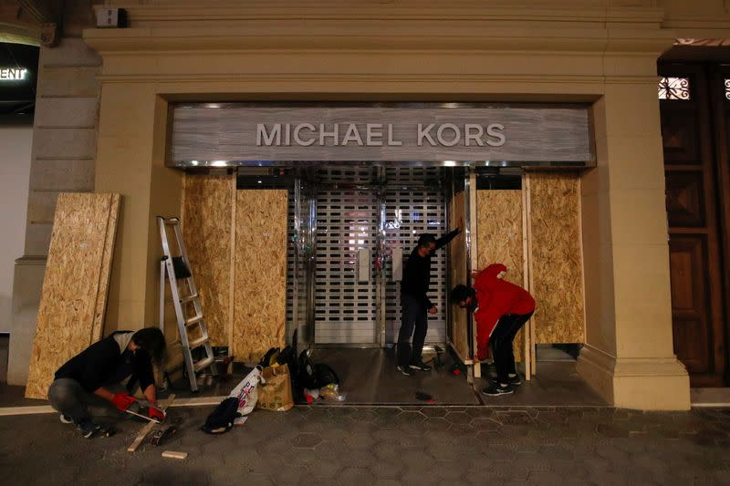 Workers cover the windows of a Michael Kors shop near the place of a protest against the arrest of Catalan rapper Pablo Hasel in Barcelona