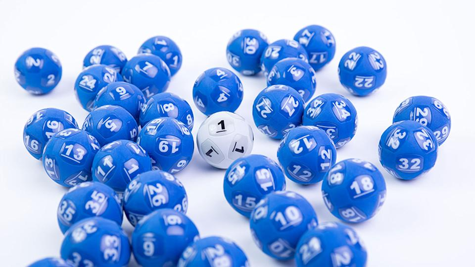 Dozens of blue lotto balls with the important white Powerball in the middle.