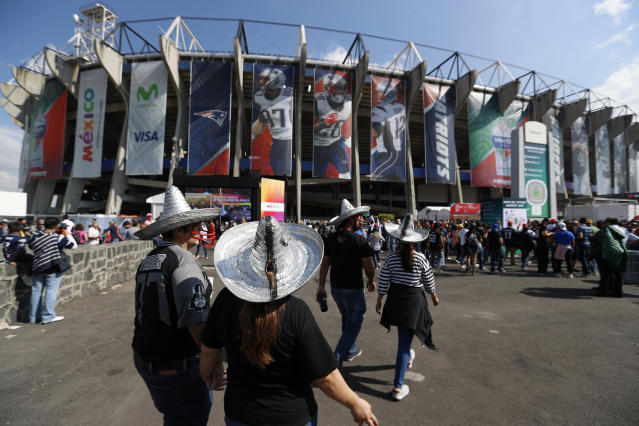 FILE - In this Nov. 19, 2017, file photo, fans arrive at Azteca stadium before an NFL football game between the Oakland Raiders and the New England Patriots in Mexico City. The NFL is moving its five games scheduled for London and Mexico City this season back to U.S. stadiums because of the coronavirus pandemic. All five regular-season games will now be played at the stadiums of the host teams. (AP Photo/Eduardo Verdugo, File)