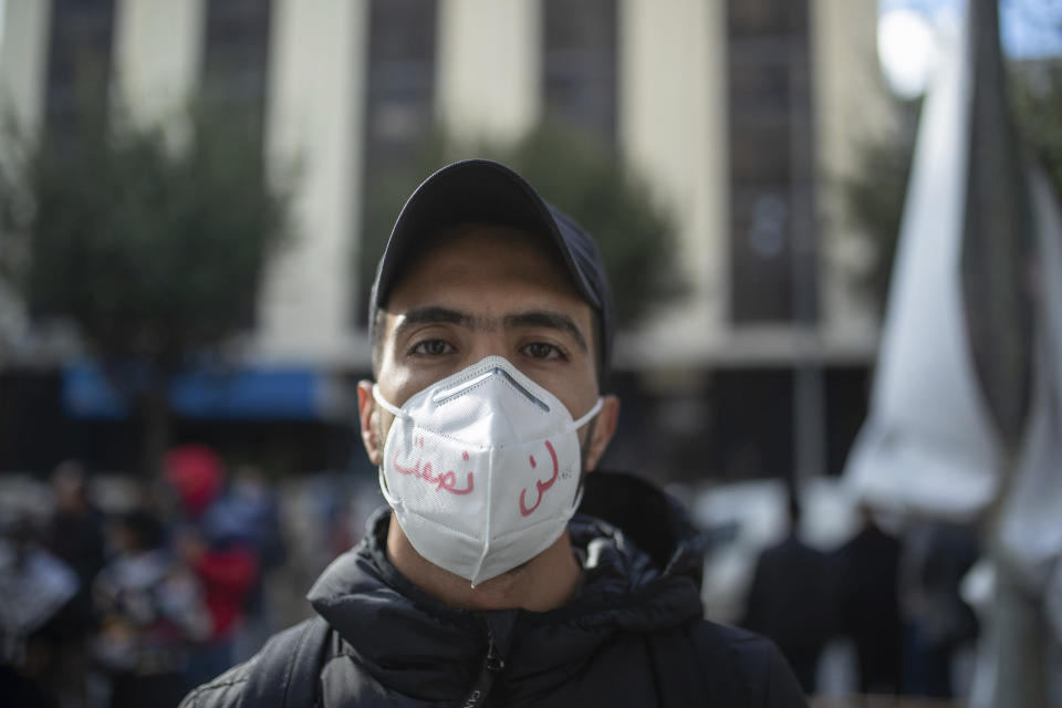 "A young man wearing a face mask poses for a portrait during a protest on the tenth anniversary of the uprising that toppled longtime autocrat Ben Ali, during to a national lockdown after a surge in COVID-19 cases, in Tunis, Thursday, Jan. 14, 2021. Writing in Arabic on facemark reads ""We will not be silenced."" Tunisia is commemorating the 10th anniversary since the flight into exile of its iron-fisted leader, Zine El Abidine Ben Ali, pushed from power in a popular revolt that foreshadowed the so-called Arab Spring. But there will be no festive celebrations Thursday marking the revolution in this North African nation, ordered into lockdown to contain the coronavirus. (AP Photo/Mosa'ab Elshamy)"