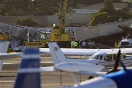Workers prepare to use cranes to extract a twin-engine Cessna Citation 525A aircraft from inside a collapsed hangar which it slammed into, bursting into flames, after it touched down last night, in Santa Monica