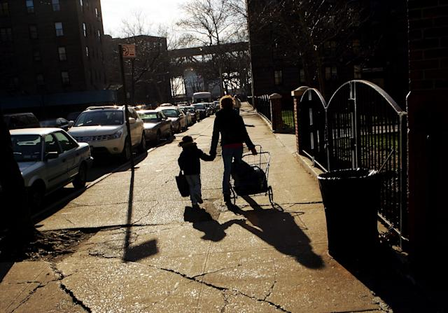 A mother holds hands with her daughter as they walk into their housing projects. (Photo: Ezra Shaw via Getty Images)