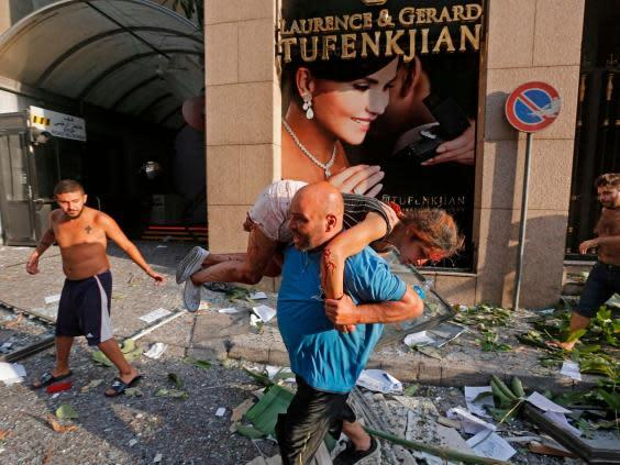 A man carries away an injured girl while walking through debris past in the Achrafiyeh district (AFP via Getty Images)