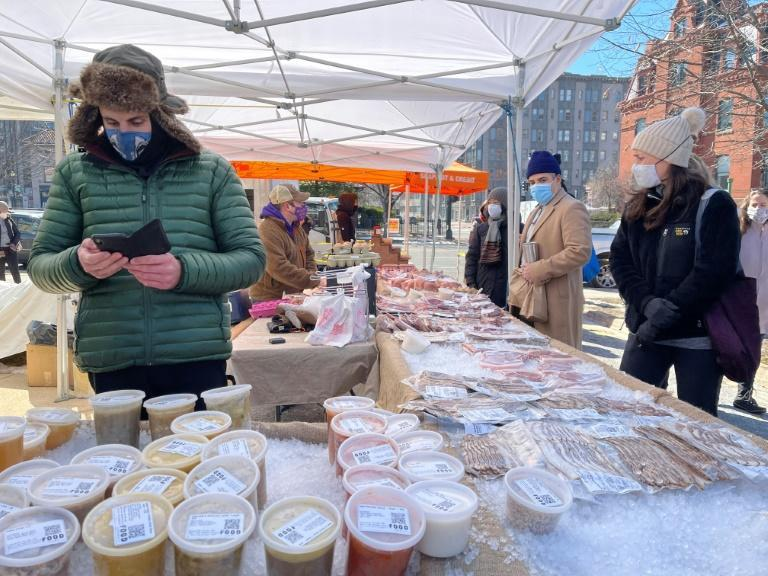 Shoppers wearing face masks keep their distance from one another at the Dupont Circle Market in Washington