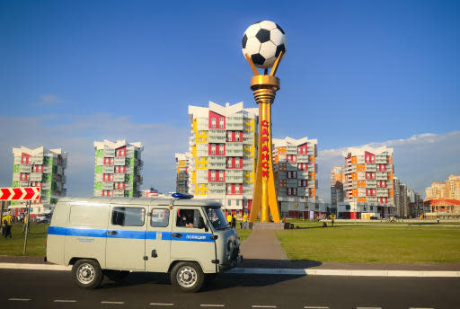 A police van drives near brightly colored apartment buildings, near the Mordavia Arena, one of the stadiums where matches of the 2018 soccer World Cup are played, in Saransk, Russia, Tuesday, June 19, 2018.(AP Photo/Vadim Ghirda)