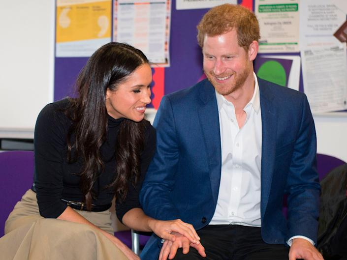Meghan Markle rests her hand on Prince Harry's hand as they sit next to each other in a public display of affection.