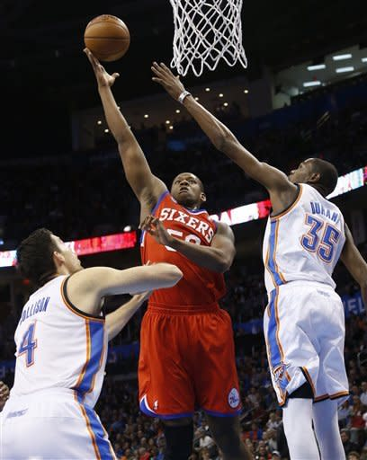 Philadelphia 76ers center Lavoy Allen (50) shoots between Oklahoma City Thunder forwards Nick Collison (4) and Kevin Durant (35) in the first quarter of an NBA basketball game in Oklahoma City, Friday, Jan. 4, 2013. (AP Photo/Sue Ogrocki)