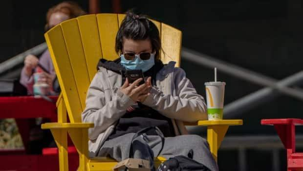 A woman checks her phone while sitting outside in Ottawa during sunny spring weather on April 3, 2021.