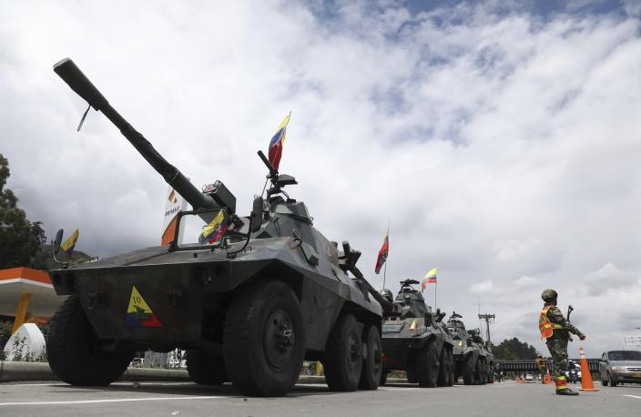 Soldiers and army tanks guard toll booths to keep protesters from damaging them, on the outskirts of Bogota, Colombia, Tuesday, May 4, 2021. Colombia's finance minister resigned on Monday following five days of protests over a tax reform proposal that left at least 17 dead. (AP Photo/Fernando Vergara)