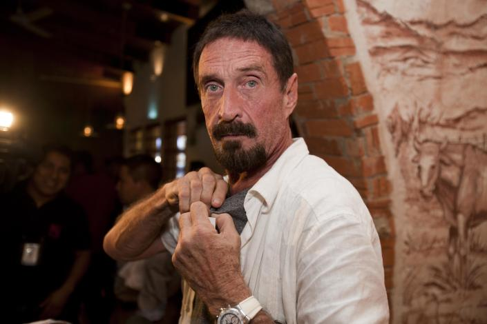 """Software company founder John McAfee adjusts a microphone in preparation for an interview in Guatemala City, Tuesday, Dec. 4, 2012. McAfee, 67, has been identified as a """"person of interest"""" in the killing of his neighbor in Belize, 52-year-old Gregory Faull. Police are urging McAfee to come in for questioning. The anti-virus company founder fled Belize and is seeking political asylum in Guatemala, according to his lawyer Telesforo Guerra. (AP Photo/Moises Castillo)"""