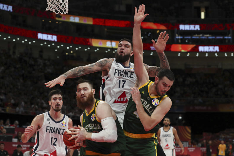 Vincent Poirier of France battles the ball with Aron Baynes and Chris Goulding of Australia during their third placing match for the FIBA Basketball World Cup at the Cadillac Arena in Beijing, Saturday, Sept. 13, 2019. (AP Photo/Ng Han Guan)