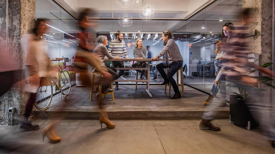 Happy entrepreneur having a business meeting inside of an office while their colleagues are walking in blurred motion.
