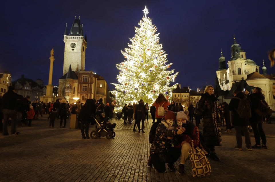 People gather by a Christmas tree illuminating the Old Town Square in Prague, Czech Republic, Saturday, Nov. 28, 2020. Prague city hall has lit up the Christmas Tre but cancelled the traditional Christmas markets due to a record surge in coronavirus infections. (AP Photo/Petr David Josek)