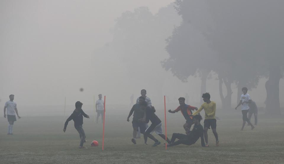 Children play football at Rajpath amid low visibility due to smog, post Diwali celebrations, in New Delhi, Sunday, 15 November. Delhi's air quality turned severe on Diwali with stubble burning accounting for 32 percent of the city's PM2.5 pollution and calm winds worsening the situation as they allowed the accumulation of pollutants.