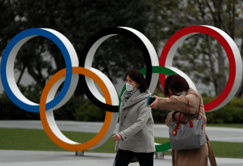 Passersby wearing protective face masks, following an outbreak of the coronavirus disease (COVID-19), walk past the Olympic rings in front of the Japan Olympics Museum, in Tokyo, Japan March 30, 2020. REUTERS/Issei Kato