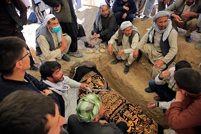 Afghan men bury a victim of deadly bombings on May 8 near a school, at a cemetery west of Kabul, Afghanistan, on May 9, 2021. The Interior Ministry said Sunday the death toll in the horrific bombing at the entrance to a girls' school in the Afghan capital has soared to some 50 people, many of them pupils between 11 and 15 years old, and the number of wounded in Saturday's attack has also climbed to more than 100.