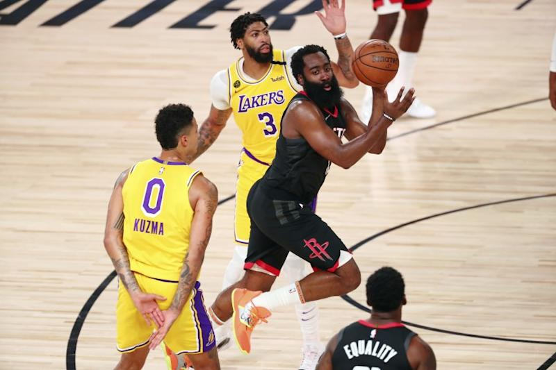 Rockets guard James Harden passes the ball between Lakers forward Kyle Kuzma and forward Anthony Davis.